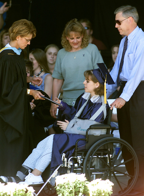 DEN04D:CRIME-SHOOTING:DENVER,22MAY99 - Lisa Kreutz, one of the Columbine High School seniors wounded in the shooting attack at the school receives her diploma from her wheelchair at commencement ceremonies May 22 with her mother center Sheryl and father Ken right.  Two students of the class of 1999 were killed in the shootings and three injured. rtw/Photo by Rick Wilking