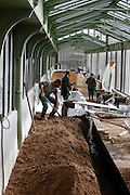 Desert and Arid Lands Glasshouse, 1930s, Jardin des Plantes, Museum National d'Histoire Naturelle, Paris, France. Low angle view of gardeners filling the troughs in which the cactuses will be planted with a mixture of loam and sand.