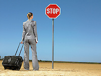 Business woman with luggage standing in front of stop sign in desert back view