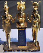 three gods statuette for King Osorkon II (depicts the family of the god Osiris) Osiris is flanked by Horus (left) and Isis (right).