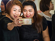 "29 NOVEMBER 2016 - BANGKOK, THAILAND:  Women take a ""selfie"" before donating alms to Buddhist monks at a special ""tak bat"" or merit making ceremony in the Ratchaprasong skywalk of the Bangkok BTS system. The tak bat was to honor Bhumibol Adulyadej, the Late King of Thailand. Food and other goods were given to the monks, who in turn gave the items to charities that will distribute them to Bangkok's poor. More than 100 Buddhist monks participated in the merit making ceremony. The ceremony was organized by the merchants in the Ratchaprasong Intersection, which includes some of Bangkok's most upscale shopping centers.     PHOTO BY JACK KURTZ"