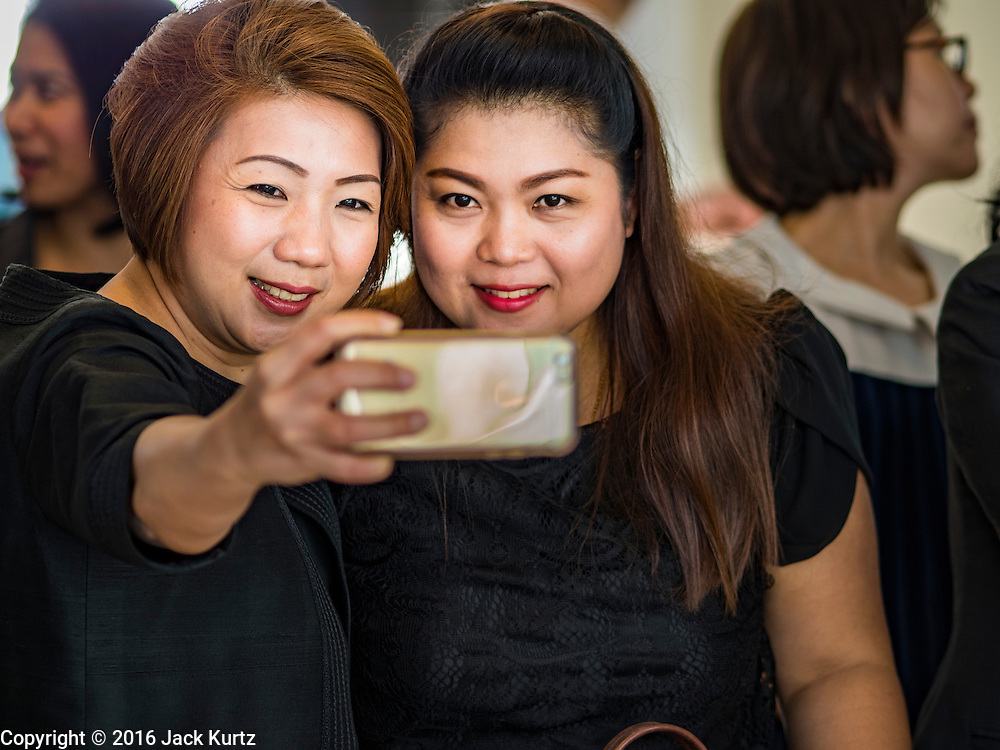 """29 NOVEMBER 2016 - BANGKOK, THAILAND:  Women take a """"selfie"""" before donating alms to Buddhist monks at a special """"tak bat"""" or merit making ceremony in the Ratchaprasong skywalk of the Bangkok BTS system. The tak bat was to honor Bhumibol Adulyadej, the Late King of Thailand. Food and other goods were given to the monks, who in turn gave the items to charities that will distribute them to Bangkok's poor. More than 100 Buddhist monks participated in the merit making ceremony. The ceremony was organized by the merchants in the Ratchaprasong Intersection, which includes some of Bangkok's most upscale shopping centers.     PHOTO BY JACK KURTZ"""