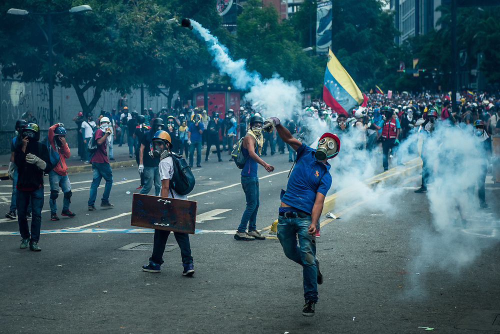 CARACAS, VENEZUELA - MAY 20, 2017:  Anti-government protesters throw back tear gas canisters that were launched toward them by the National Police, who were heavily tear gassing and firing rubber bullets and buckshot at them.  The streets of Caracas and other cities across Venezuela have been filled with tens of thousands of demonstrators for nearly 100 days of massive protests, held since April 1st. Protesters are enraged at the government for becoming an increasingly repressive, authoritarian regime that has delayed elections, used armed government loyalist to threaten dissidents, called for the Constitution to be re-written to favor them, jailed and tortured protesters and members of the political opposition, and whose corruption and failed economic policy has caused the current economic crisis that has led to widespread food and medicine shortages across the country.  Independent local media report nearly 100 people have been killed during protests and protest-related riots and looting.  The government currently only officially reports 75 deaths.  Over 2,000 people have been injured, and over 3,000 protesters have been detained by authorities.  PHOTO: Meridith Kohut
