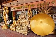 "05 JULY 2011 - BANGKOK, THAILAND:   Buddha statues for sale on Bamrung Muang Street in Bangkok. Thanon Bamrung Muang (Thanon is Thai for Road or Street) is Bangkok's ""Street of Many Buddhas."" Like many ancient cities, Bangkok was once a city of artisan's neighborhoods and Bamrung Muang Road, near Bangkok's present day city hall, was once the street where all the country's Buddha statues were made. Now they made in factories on the edge of Bangkok, but Bamrung Muang Road is still where the statues are sold. Once an elephant trail, it was one of the first streets paved in Bangkok, it is the largest center of Buddhist supplies in Thailand. Not just statues but also monk's robes, candles, alms bowls, and pre-configured alms baskets are for sale along both sides of the street.         PHOTO BY JACK KURTZ"