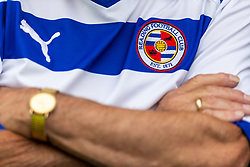 Detail of the badge on the shirt of a Reading fan in the stands