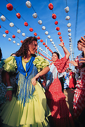 Europe, Spain, Sevilla (also known as Seville) women in flamenco dresses dancing at annual Feria de Abril festival