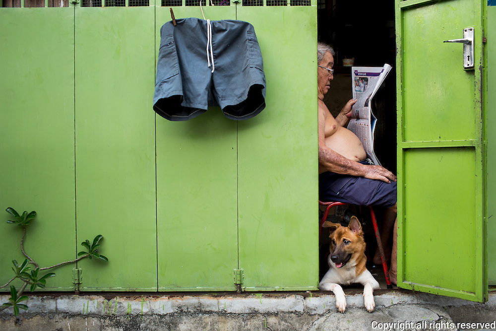 A man reads the morning paper while his dog watches the street in a George Town housing complex. Penang, Malaysia