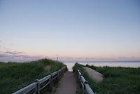 The trail leads through beach grass to the ocean at sunset at Basinhead beach in PEI, Canada.