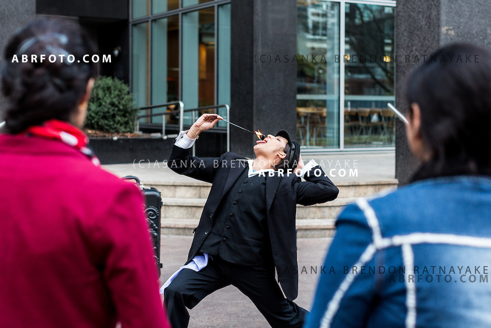 A street performer places fire in his mouth as pedestrians look on Melbourne Victoria Australia