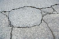 Cracks in the surface of a concrete street.