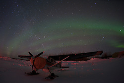 An airplane waits out the night beneath the northern lights in the Arctic Circle.