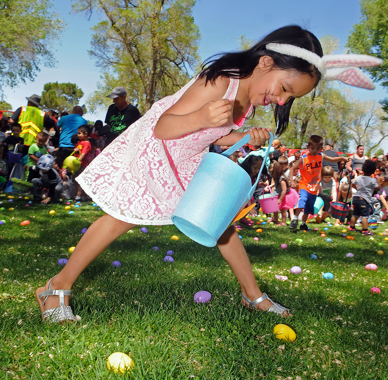 jt041517j/a sec/jim thompson/  Mia Hidalgo-5 prepares to pounce on a egg at the Victory Outreach Albuquerque Church's HOPE Easter Egg Hunt and care Basket Giveaway at Roosevelt Park.  Saturday April 15, 2017. (Jim Thompson/Albuquerque Journal)