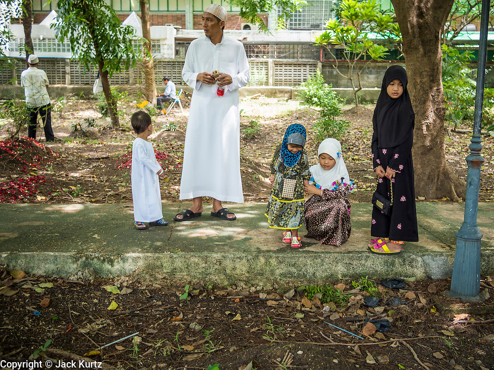 "08 AUGUST 2013 - BANGKOK, THAILAND: A family walks through the Muslim cemetery next to Haroon Mosque after Eid al-Fitr services in Bangkok. Tending graves is a tradition on Eid. Eid al-Fitr is the ""festival of breaking of the fast,"" it's also called the Lesser Eid. It's an important religious holiday celebrated by Muslims worldwide that marks the end of Ramadan, the Islamic holy month of fasting. The religious Eid is a single day and Muslims are not permitted to fast that day. The holiday celebrates the conclusion of the 29 or 30 days of dawn-to-sunset fasting during the entire month of Ramadan. This is a day when Muslims around the world show a common goal of unity. The date for the start of any lunar Hijri month varies based on the observation of new moon by local religious authorities, so the exact day of celebration varies by locality.      PHOTO BY JACK KURTZ"