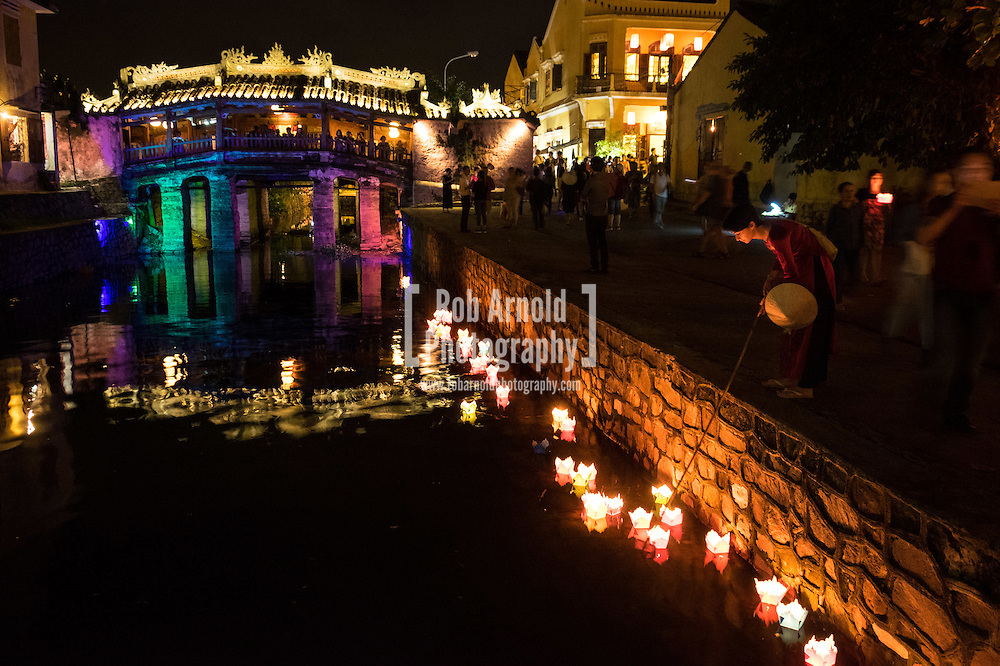A woman dressed in a traditional vietnamese Ao Dai places a candle into the water next to the historical Japanese Covered Bridge in Hoi An, Vietnam.