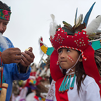 Bradley Edaakie helps his grandson Arlo Edaakie Jr. prepare for the Zuni parade Friday with their Supia dance group.
