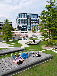People relaxing  at modern Vasco Da Gamma Platz in new Hafencity property development in Hamburg Germany