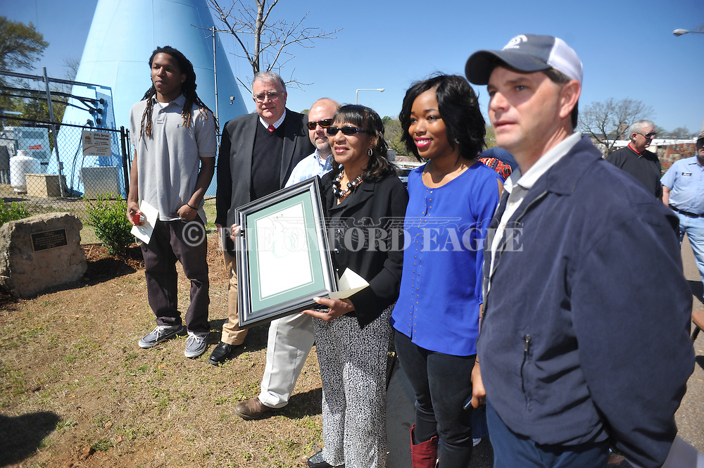 The water tower next to the Oxford Park Commission was dedicated to the late John Stevenson Madkins Jr., who worked for 47 years in the city water department, during a ceremony in Oxford, Miss. on Wednesday, April 9, 2014. Madkins' son D'Marius Madkins, widow Ruby Madkins, and daughter Angel Madkins hold a city resolution following the ceremony.