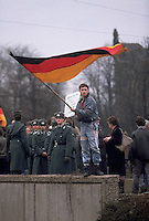 December 1989, Dresden, East Germany --- Waiting for the arrival of West German chancellor Helmut Kohl during his first visit to East Germany since the fall of the Berlin Wall, a young man waves a West German flag in front of a group of East German soldiers. Dresden, East Germany. --- Image by © Owen Franken/CORBIS