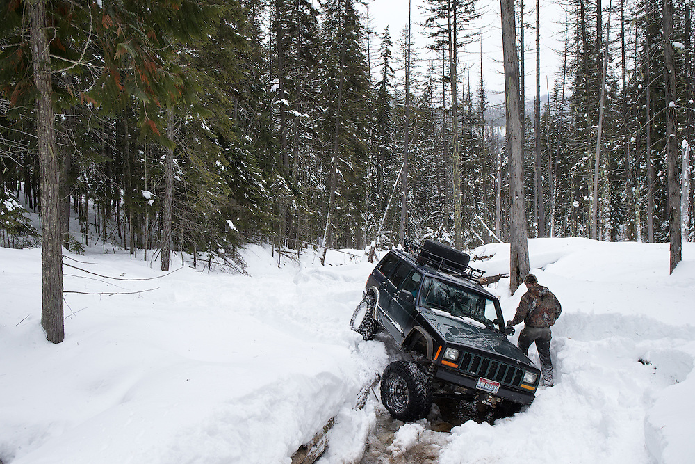 GABE GREEN/Press<br /> <br /> John Schirmer walks back to his 2000 Jeep Cherokee after driving it over an embankment, popping out  a ball joint and breaking the front axle, while wheeling with the North Idaho Trailblazers Saturday on private land near Mullan, Idaho.