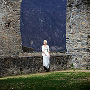 a woman in a white period dress is sitting on a wall at a castle