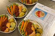 "Menu specification of a Business Class in-flight airline salmon meal are compared next to finished dishes in the world's largest independent provider of airline catering and provisioning services, Gate Gourmet, reaches out to add the last items in the company's factory on the southern perimeter road at Heathrow Airport, West London. Gate Gourmet serve more than 200 million meals on 2 million airline flights a year to their 250-plus airline customers at more than 100 airport locations around the globe. Apart from creating the bespoke meals for an airline's culture and ethnic demands, that pack the pre-flight carts, deliver and load into the aircraft galleys and afterwards, they dispose of the waste and strip, wash and sterilize the equipment. From writer Alain de Botton's book project ""A Week at the Airport: A Heathrow Diary"" (2009). ."
