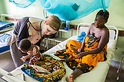 Dr Siobhan Neville examines  3 day old Samson on the children's ward during the daily rounds.  The rounds are attended by all the medical staff who work on that ward, doctors, nurses and attendants.  St Walburg's Hospital, Nyangao. Lindi Region, Tanzania.