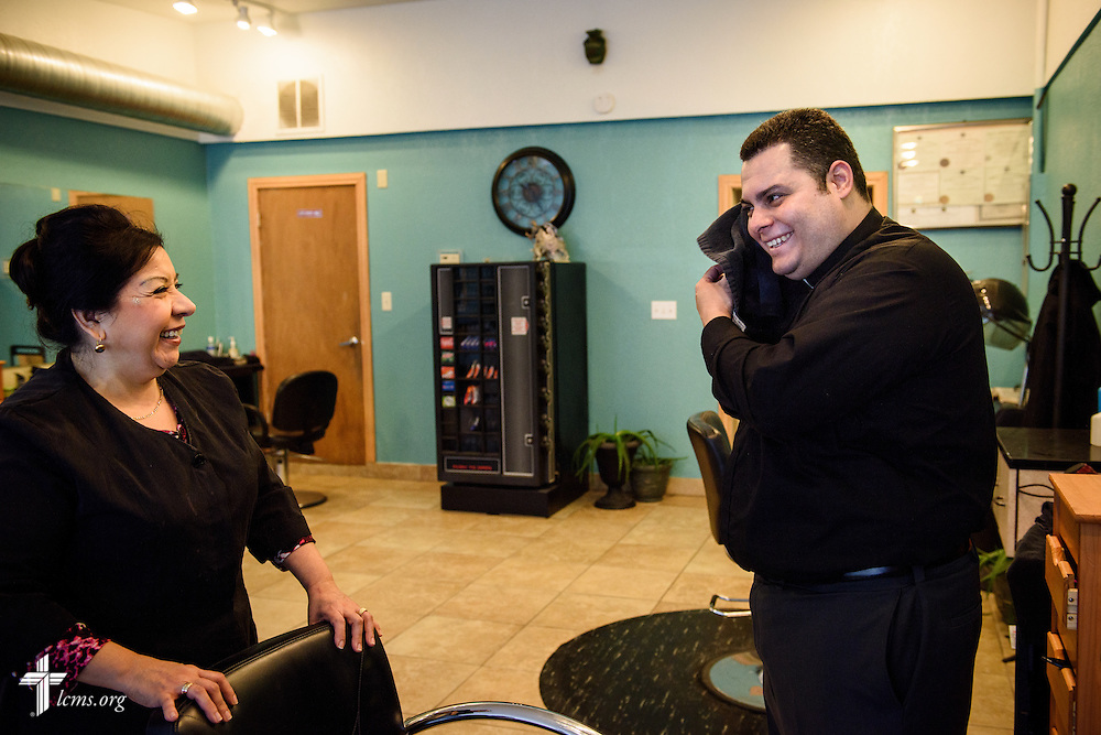"Vicar David Blas, missionary-at-large at LCMS Sheboygan County Hispanic Outreach and St. John's Lutheran Church of Plymouth, Wis., chats with Reyna ""Carolina"" Perez during a haircut and wash at Carolina's Hair Styling on Thursday, Jan. 28, 2016, in Sheboygan, Wis. LCMS Communications/Erik M. Lunsford"