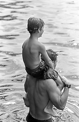 man carrying a boy on his shoulders while walking in a lake