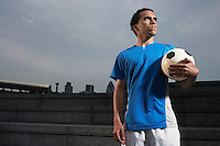 Man holding soccer ball outdoors
