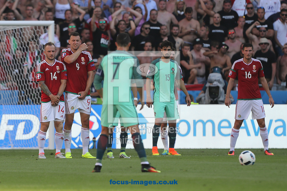 Gergo Lovrencsics of Hungary and Adam Szalai of Hungary in the wall face a free kick from Cristiano Ronaldo of Portugal during the UEFA Euro 2016 match at Stade de Lyons, Lyons<br /> Picture by Paul Chesterton/Focus Images Ltd +44 7904 640267<br /> 22/06/2016