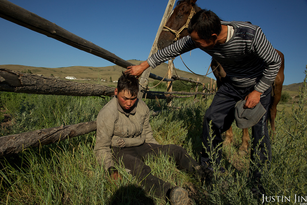 A drunken herder collapses next to his horse near a barn in a village outside the capital Kyzyl in Tuva Republic, Russia. Alcoholism is rife in the region.