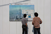 Two men read details of the new Tokyo Sky Tree  on the wall of its construction site. Tokyo, Japan. Monday June 21st 2010. In this image the unfinished telecommunication tower stands at 398 metres high, Upon completion it will measure 634 metres from top to bottom, becoming the tallest structure in East Asia.