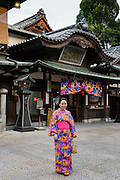 Matsuyama, September 3 2015 - Dogo Onsen, Japan's oldest hot spring, celebrate the 120th anniversary in 2014 by creating an art festival. The artist invited in 2015 is Japanese photographer Mika NINAGAWA.<br /> Girl wearing rental kimono designed by MIka NINAGAWA.