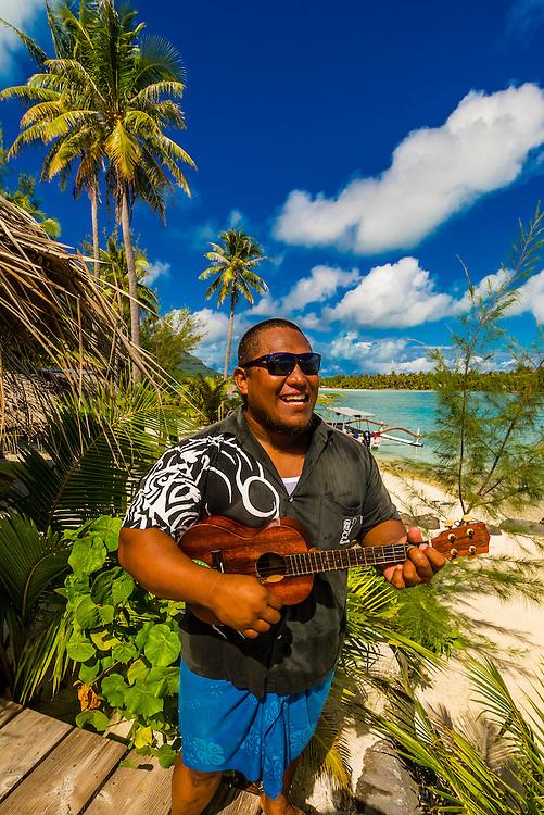 Polynesian man playing a ukelele, Haapiti Motu (a small private island) off Bora Bora, Society Islands, French Polynesia.