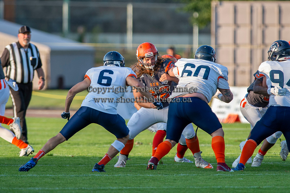 KELOWNA, BC - AUGUST 3:  JJ Heaton #62 of Okanagan Sun blocks Jericho Schmidt LB #6 and Damian Person DL #60 of Kamloops Broncos  at the Apple Bowl on August 3, 2019 in Kelowna, Canada. (Photo by Marissa Baecker/Shoot the Breeze)