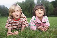Portrait of two boys (7-9) lying in meadow