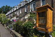 The community library box of books and terraced housing on Teviotdale Place alongside the Waters of Leith, in Edinburgh, on 26th June 2019, in Edinburgh, Scotland.