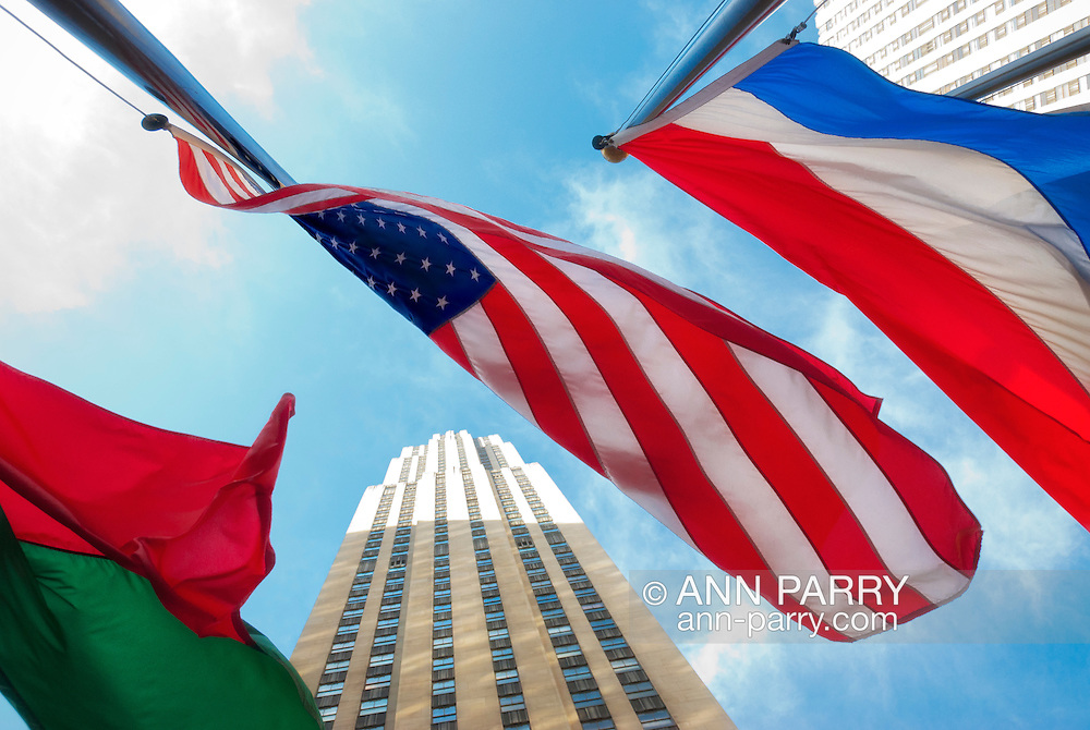 At Rockefeller Plaza, the American flag (center), flag of Republic of Madagascar (left), and national flag of the Netherlands (right), flying in windy day, in front of 30 Rockefeller Center, GE Building, seen from low angle, in Manhattan, New York City, USA, on January 24, 2012. <br /> All 3 are official national flags of member states of United Nations:<br /> At left is flag of Republic of Madagascar, with two equal horizontal rectangles - top red and bottom green, though not included in this view is the left vertical white section.<br /> At center, is flag of the United States of America has 50 small 5-pointed white stars, representing the 50 states of the union, in nine offset horizontal rows on a field of blue in upper corner, and horizontal 13 stripes alternating in color, 7 red stripes and 6 white stripes, representing the original 13 colonies.<br /> At right, is flag of the Netherlands is three equal horizontal stripes - red (bright vermilion) stripe on top, white (silver) stripe in middle, and blue (cobalt blue) stripe on bottom.