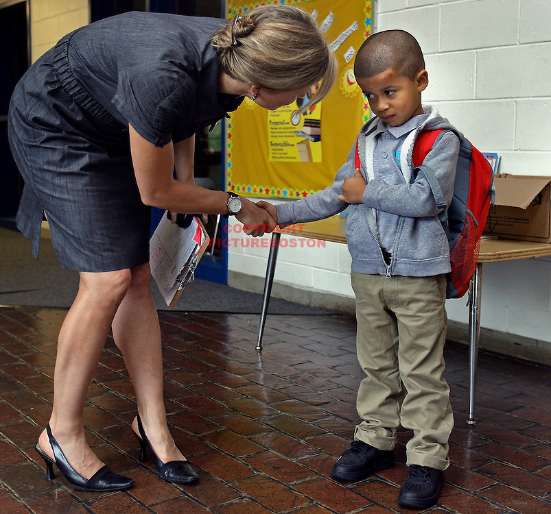 Yeremy Araujo is calmed by Kate Carpenter Bernier, the principal of the Ell charter school, on the first day of school at the Jamaica Plain school, today, September 6, 2011. Staff photo by Mark Garfinkel