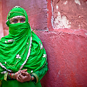 A Mulsim woman a green scarf or as it is called locally a duptta,  smiles for the camera with just her eyes.