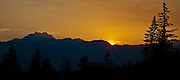 The last light of the sun flares over the silhouette of The Brothers mountain and the Olympic Mountain Range as viewed from the Kitsap Peninsula, WA USA