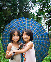 Two young girls holding an umbrella, Bohol, Philippines..