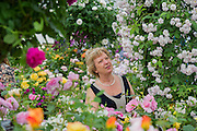 A visitor enjoys the flowers on the David Austin stand. The Chelsea Flower Show 2014. The Royal Hospital, Chelsea, London, UK.  19 May 2014