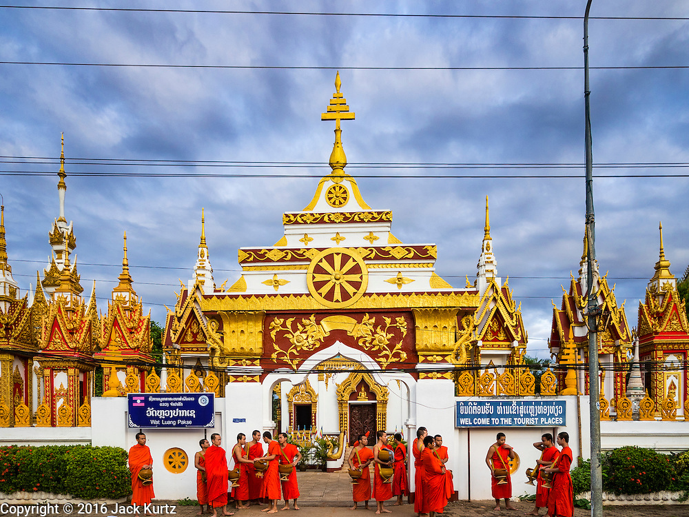 16 JUNE 2016 - PAKSE, CHAMPASAK, LAOS: Monks gather in front of the prayer hall at Wat Luang before going out on their morning Tak Bat, or alms rounds, in Pakse. Pakse is the capital of Champasak province in southern Laos. It sits at the confluence of the Xe Don and Mekong Rivers. It's the gateway city to 4,000 Islands, near the border of Cambodia and the coffee growing highlands of southern Laos.       PHOTO BY JACK KURTZ