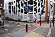 On London's congestion zone boundary, arrow street signs and car park on Commercial Road, Spitalfields, East London UK.  The car park stands on the site where one of the Jack the Ripper's victims were murdered.