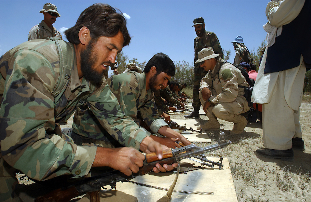 Afghan soldiers are supervised by their U.S. Army special forces trainers as they assemble assault rifles during a training competition May 27, 2002 at an Afghan National Army (ANA) training facility in Kabul, Afghanistan. U.S. Special Forces conduct  ten week training courses for the Afghan Army in the hope that a better trained military will mean a more stable Afghanistan.
