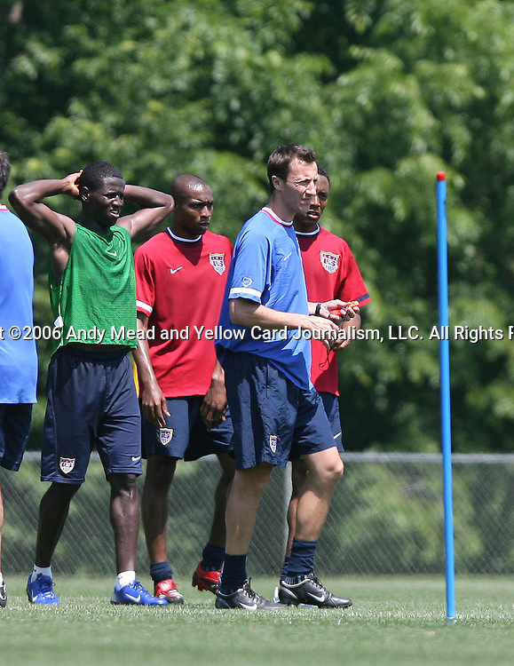 Team Trainer Pierre Barrieu (in blue) explains a fitness exercise to players, including Eddie Johnson (l), Eddie Pope (center), and Cory Gibbs (behind) on Wednesday, May 17th, 2006 at SAS Soccer Park in Cary, North Carolina. The United States Men's National Soccer Team held a training session as part of their preparations for the upcoming 2006 FIFA World Cup Finals being held in Germany.