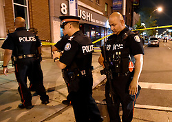Police secure the scene of a mass casualty incident in Toronto, ON, Canada on Sunday, July 22, 2018. A young woman has been killed and 13 others injured in a shooting incident in Toronto, Canadian police say. The Sunday night shooting happened in the Danforth and Logan avenues area. The gunman died in an exchange of fire. Among those injured is a young girl, described as in a critical condition. Police are appealing for witnesses. Photo by Nathan Denette/ABACAPRESS.COM