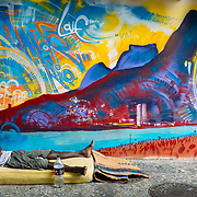 Afro-Brazilian man sleeps rough on a street with a mattress in front of a colourful mural depicting Ipanema Beach, Rio de Janeiro, Brazil