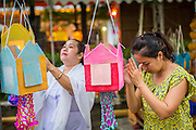 28 NOVEMBER 2012 - BANGKOK, THAILAND: Women hang lanterns and pray during Loy Krathong at Wat Yannawa in Bangkok. Loy Krathong takes place on the evening of the full moon of the 12th month in the traditional Thai lunar calendar. In the western calendar this usually falls in November. Loy means 'to float', while krathong refers to the usually lotus-shaped container which floats on the water. Traditional krathongs are made of the layers of the trunk of a banana tree or a spider lily plant. Now, many people use krathongs of baked bread which disintegrate in the water and feed the fish. A krathong is decorated with elaborately folded banana leaves, incense sticks, and a candle. A small coin is sometimes included as an offering to the river spirits. On the night of the full moon, Thais launch their krathong on a river, canal or a pond, making a wish as they do so.    PHOTO BY JACK KURTZ
